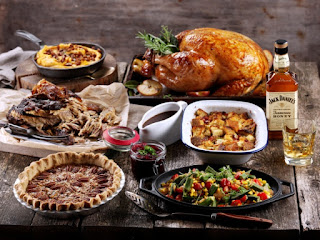 A table full of traditional Thanksgiving food and a bottle of Jack Daniel's whiskey.