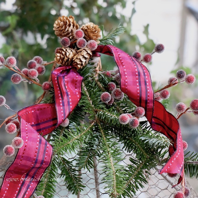 Christmas red plaid berry birdcage has a cluster of tiny gold pine cones at the top