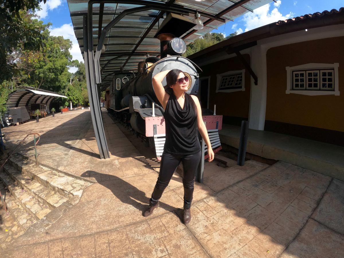 mulher de preto em uma estação de trem desativada