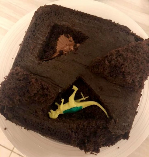 This picture shows the bottom layer of cake with two dinosaurs inserted into cut outs.