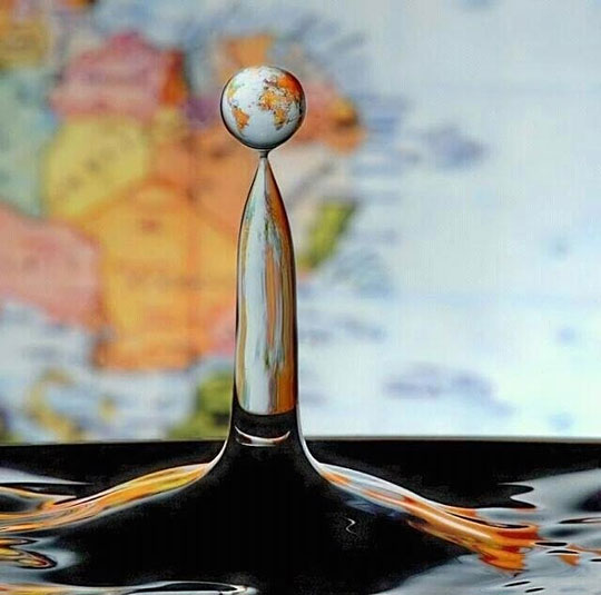 world map reflected in a water drop