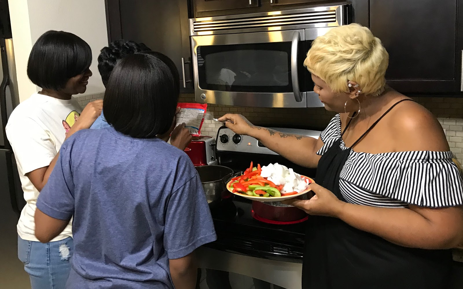 Pulling Together! Tangie Bell sharing cooking tips with daughters