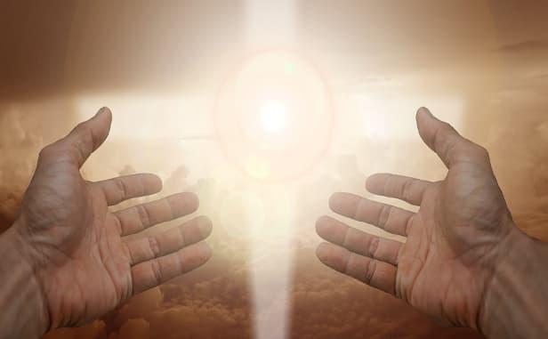 A imagem mostra mãos levantadas ao céu, em direção de uma forte luz amarela em formato de cruz. será Deus?