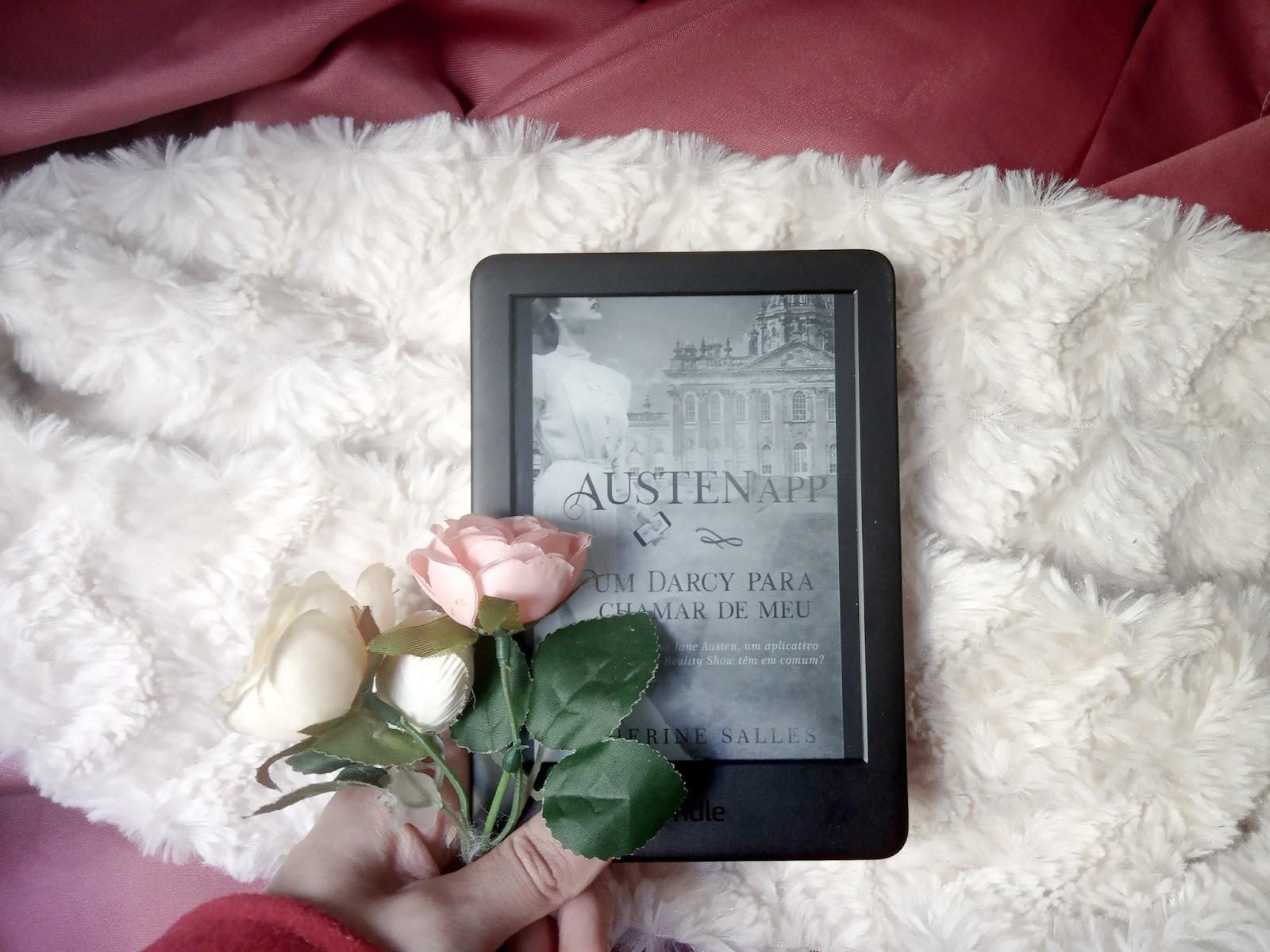 Foto com fundo mesclado de tecido liso vermelho vinho e um tecido peludo, sobre ele tem um aparelho kindle com a capa do livro AustenApp e uma mão segurando flores