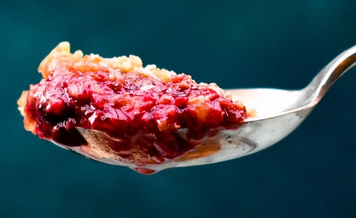 A close up of a spoonful of blackberry crumble