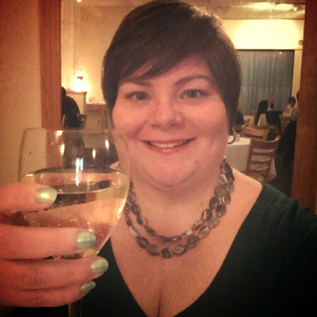 image of me sitting in a restaurant, smiling and raising my glass of white wine for a toast; I've got very short hair and am wearing contacts, a green sweater, a grey stone necklace, and green nail polish