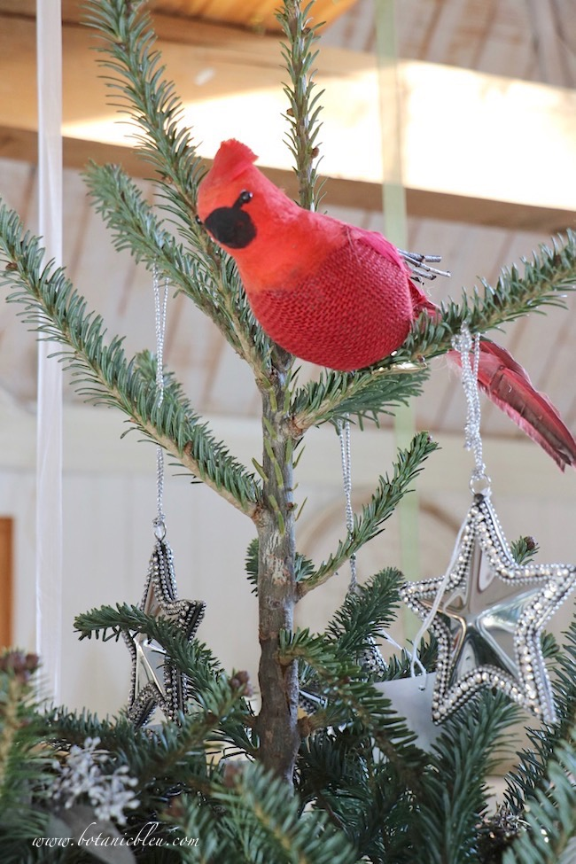A large red cardinal as a tree topper oversees all the bird's nests on the Christmas tree.