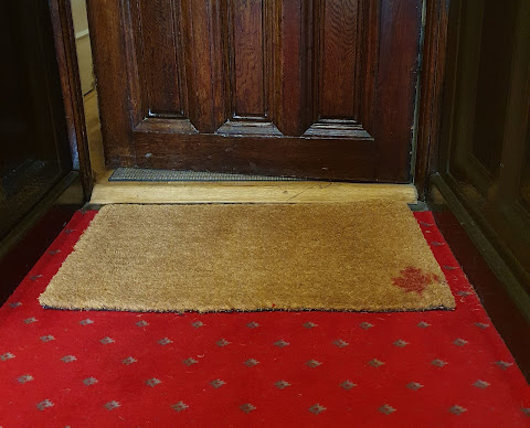 A wooden door is ajar. Before it, a cuir doormat sits on a red carpet.