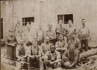 1890s photo taken in a PA logging camp, men in suspenders seated and standing, there are two women standing on the left side of the group, one man in front row is African American