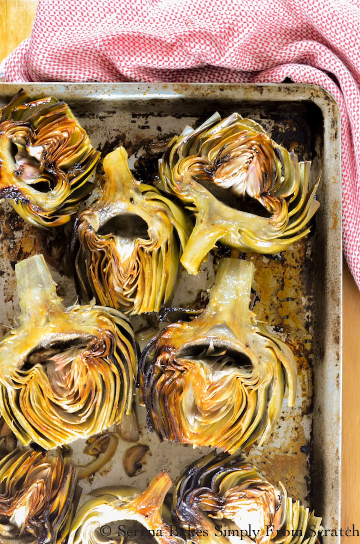 Roasted Artichokes with garlic on a baking tray with cut lemon.