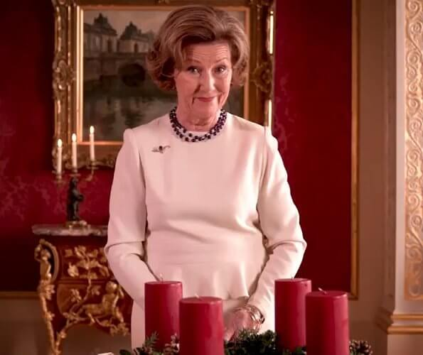 Queen Sonja of Norway wore a white suit and gold brooch, and pearl diamond necklace