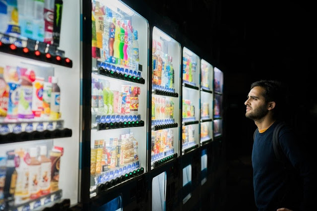 A man standing in front of a vending machine