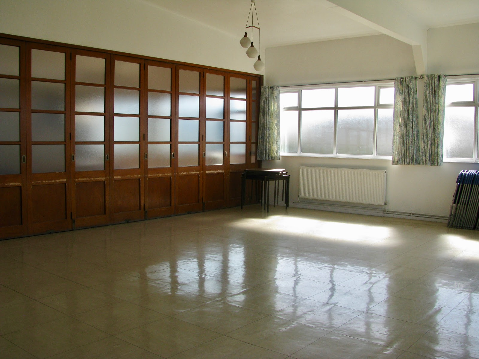 Showing floor space with linoleum floor, white walls, windows with sun shining through
