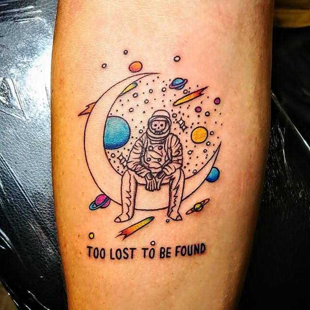 astronaut sitting on moon tattoo
