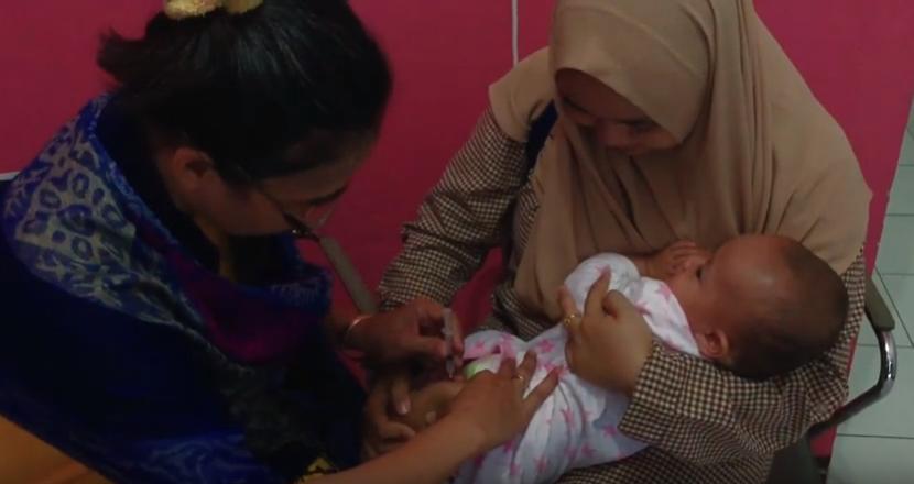 foto ibu gendong balita suktik vaksin polio