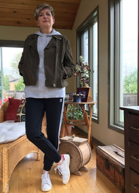 woman in Adidas sweatpants, sneakers, grey hoodie and khaki suede jacket