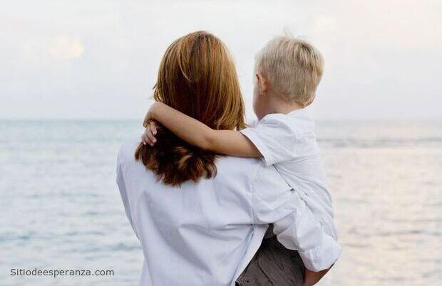 Madre cargando hijo frente al mar
