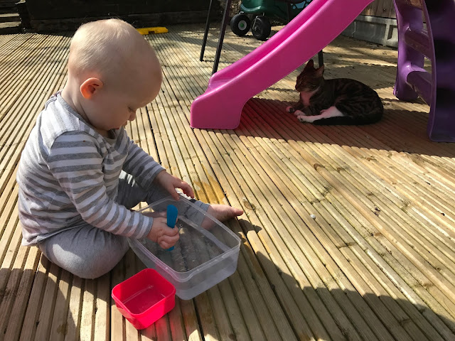 A baby playing with a spoon a tupperware box on decking with a slide in the background and a cat sitting underneath it.