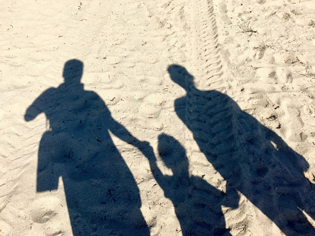 Shadow of two adults and one child in the sand at Miami Beach
