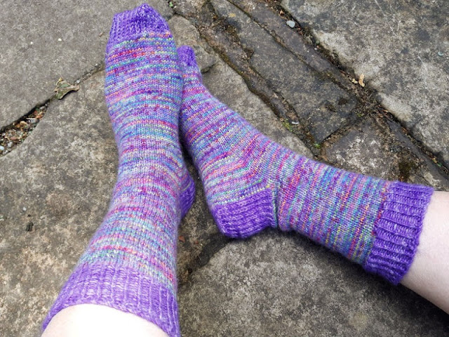 A pair of feet wearing purple striped hand knitted socks.  The background is stone flags.