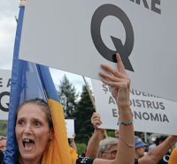 Romanian supporters of the QAnon conspiracy theories shout slogans against the government's measures to prevent the spread of COVID-19 infections, like wearing a face mask, during a rally in Bucharest in August. (AP Photo/Vadim Ghirda)