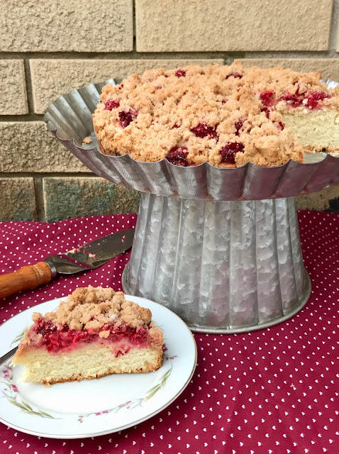 Side view of a finished lemon raspberry buckle on a cake stand with a slice of cake in front on a plate.