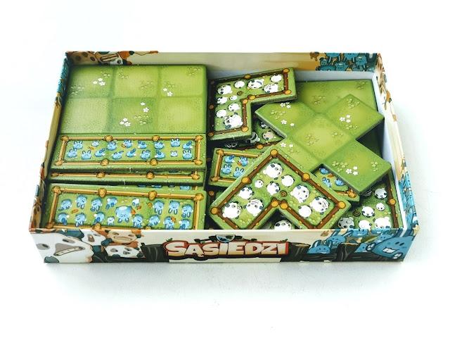 na zdjęciu otwarte pudełko a w nim elementy gry