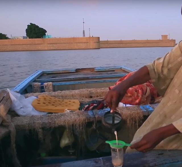 صور  السودان - خزان جبل اوليا - صياد على قاربه يعد حليبا بالشاي
