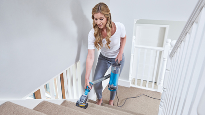 woman hoovering stairs with Shark vacuum cleaner