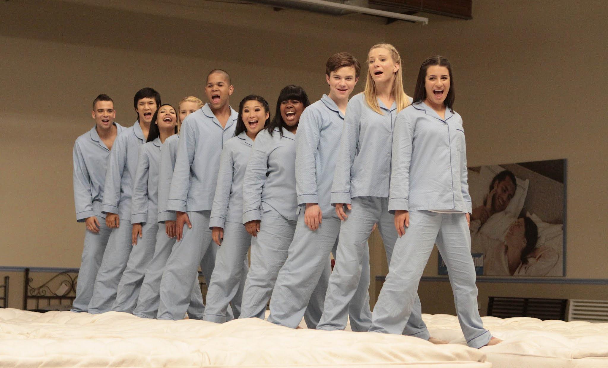 elenco de glee vestido de pijama azul claro, composto por calça e blusa de manga comprida, cantando enfileirados, um atrás do outro, em cima de um colchão enquanto gravavam um comercial para uma loja de colchões.