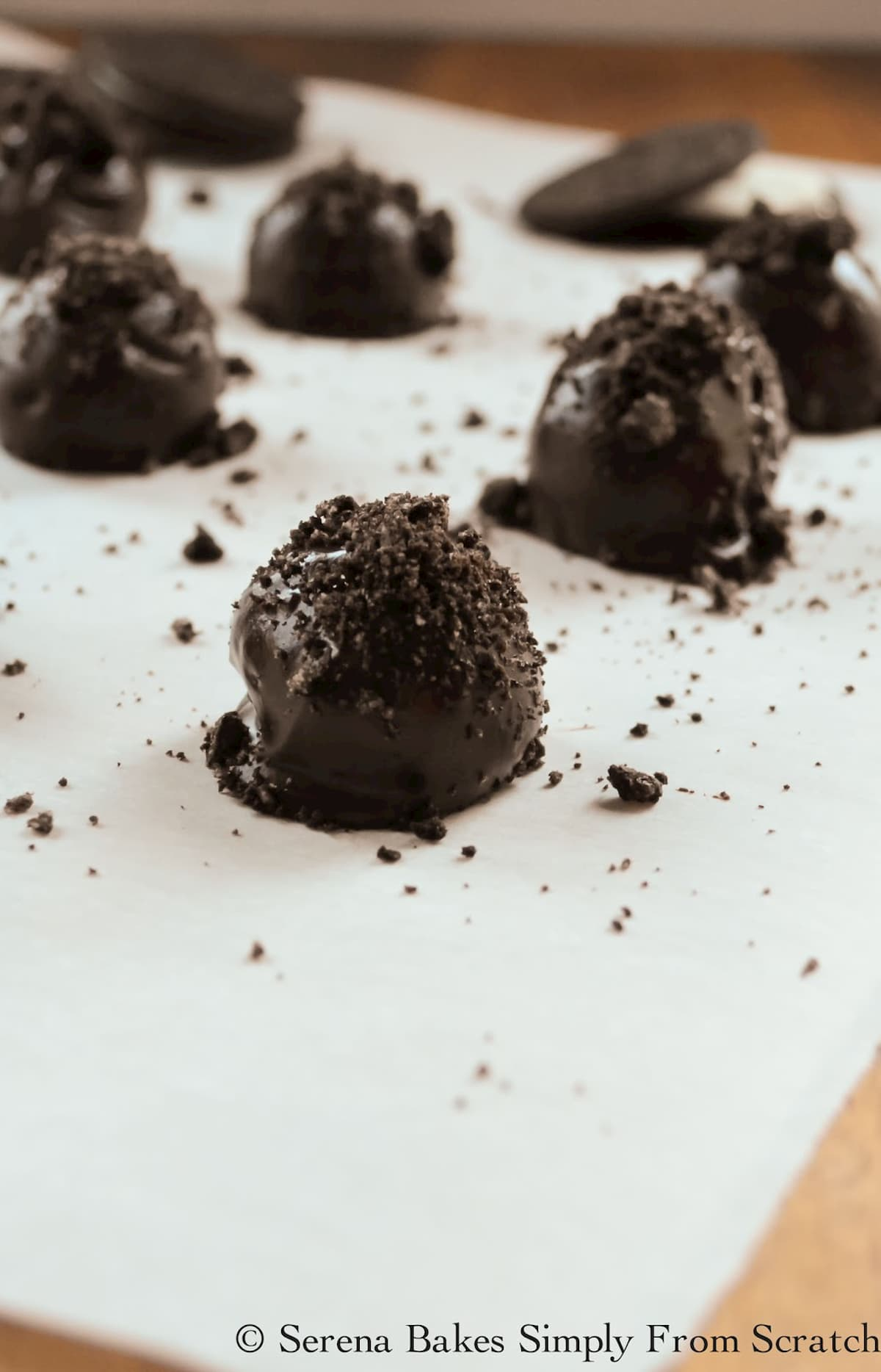Mint Oreo Cookie Balls dipped in chocolate topped with crushed oreos on a white tray.