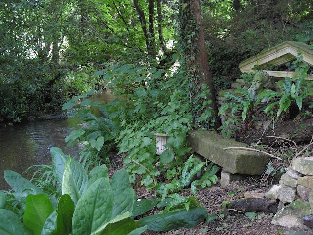 ogród leśny nad rzeką, kamienne ozdoby w ogrodzie