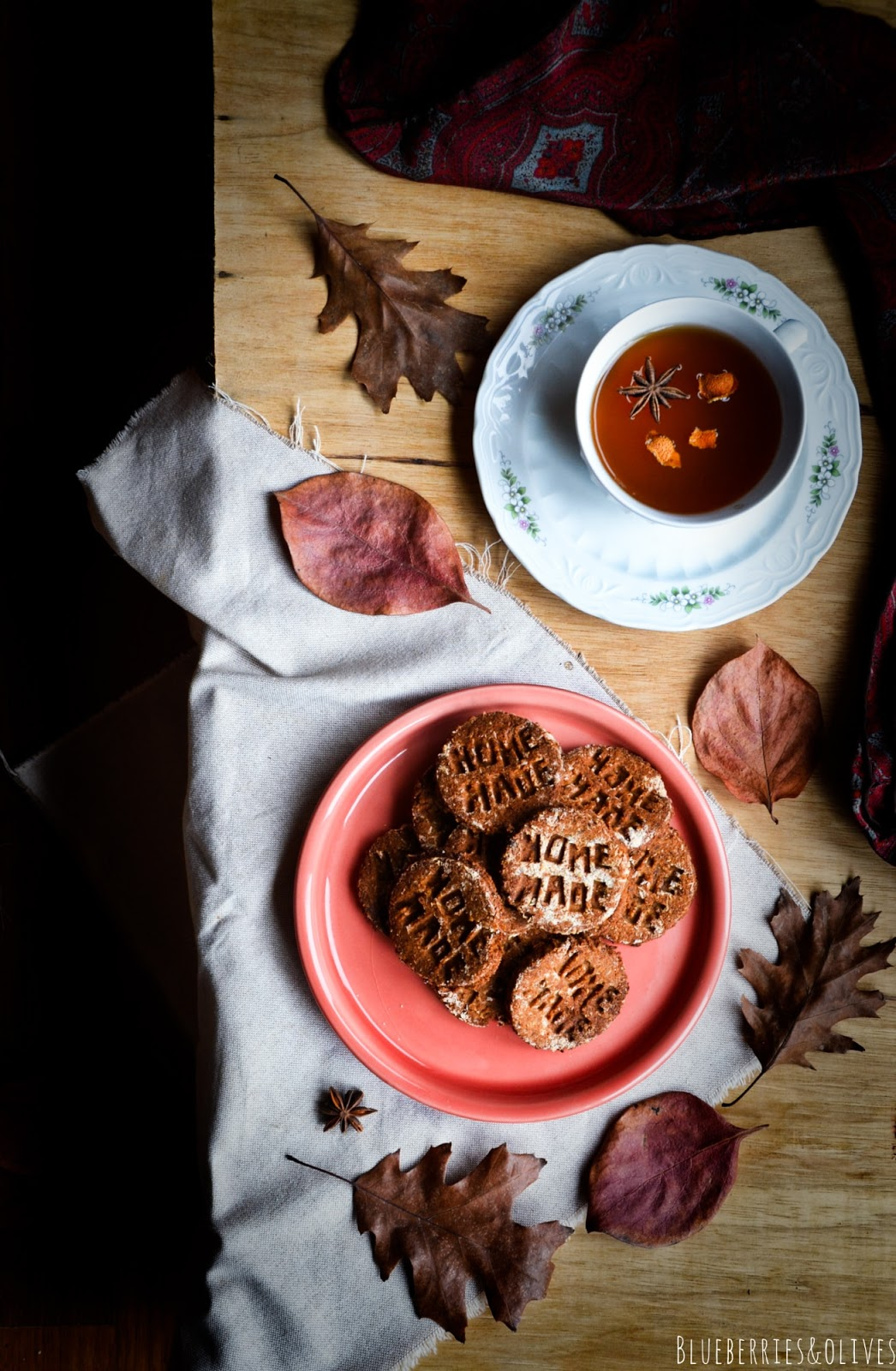 Cenital view homemade cookies on red ceramic dish, dark background, old wood, piles books with red apple on top, porcelain mug with tea, star anise and orange peels