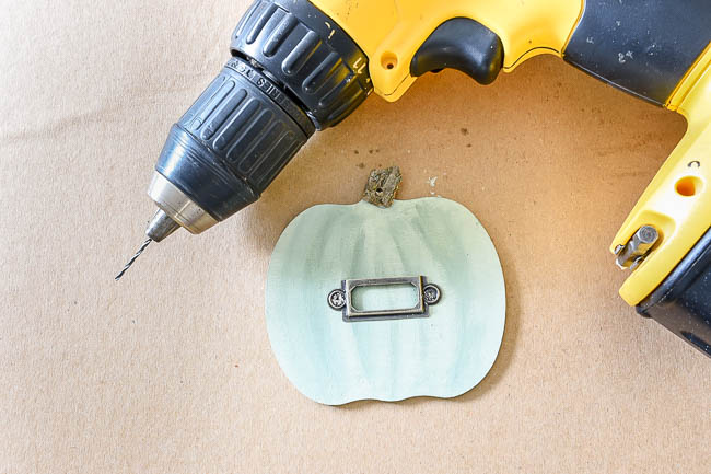 Drill holes in pumpkins for metal label holder