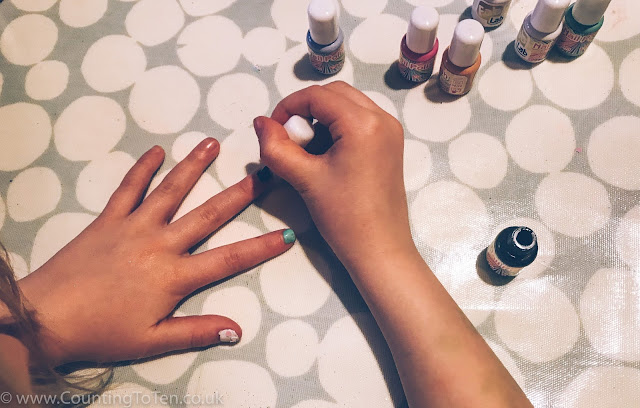 An overhead shot of my daughter painting her nails all different colours