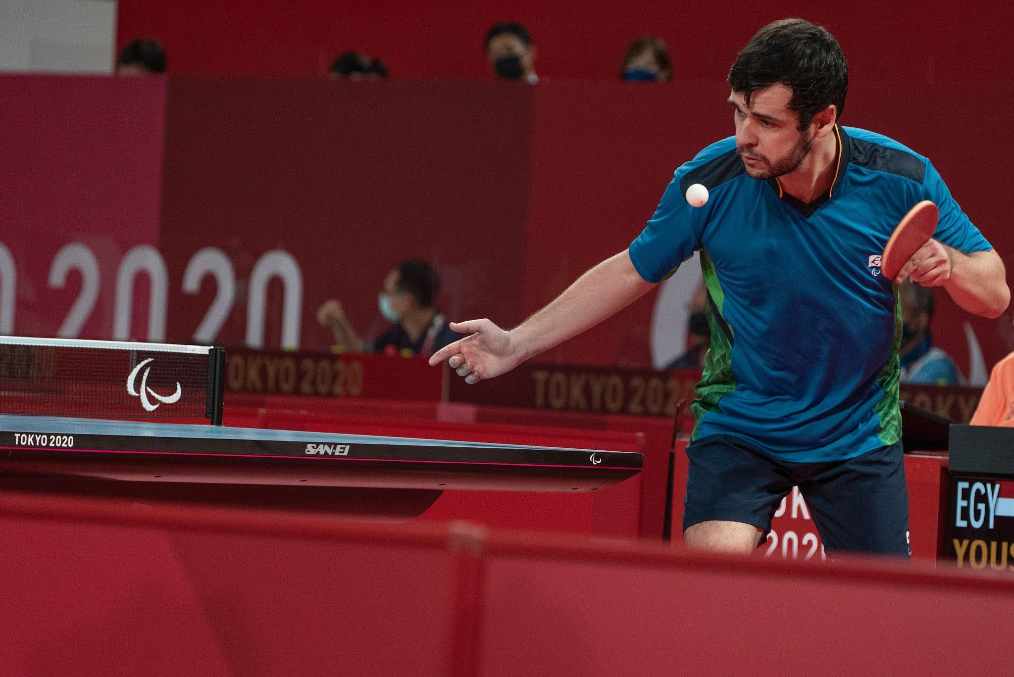 Israel Stroh está de camisa azul e saca com a raquete na mão e a bolinha no ar