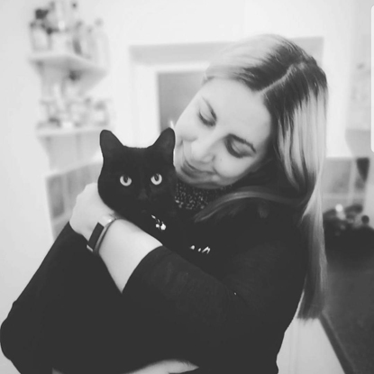 black-and-white photo of woman holding black cat