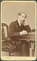 A photograph of Charles Dickens seated at a desk.