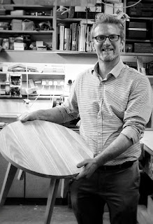 Man wearing glasses holding a coffee table which he has made.