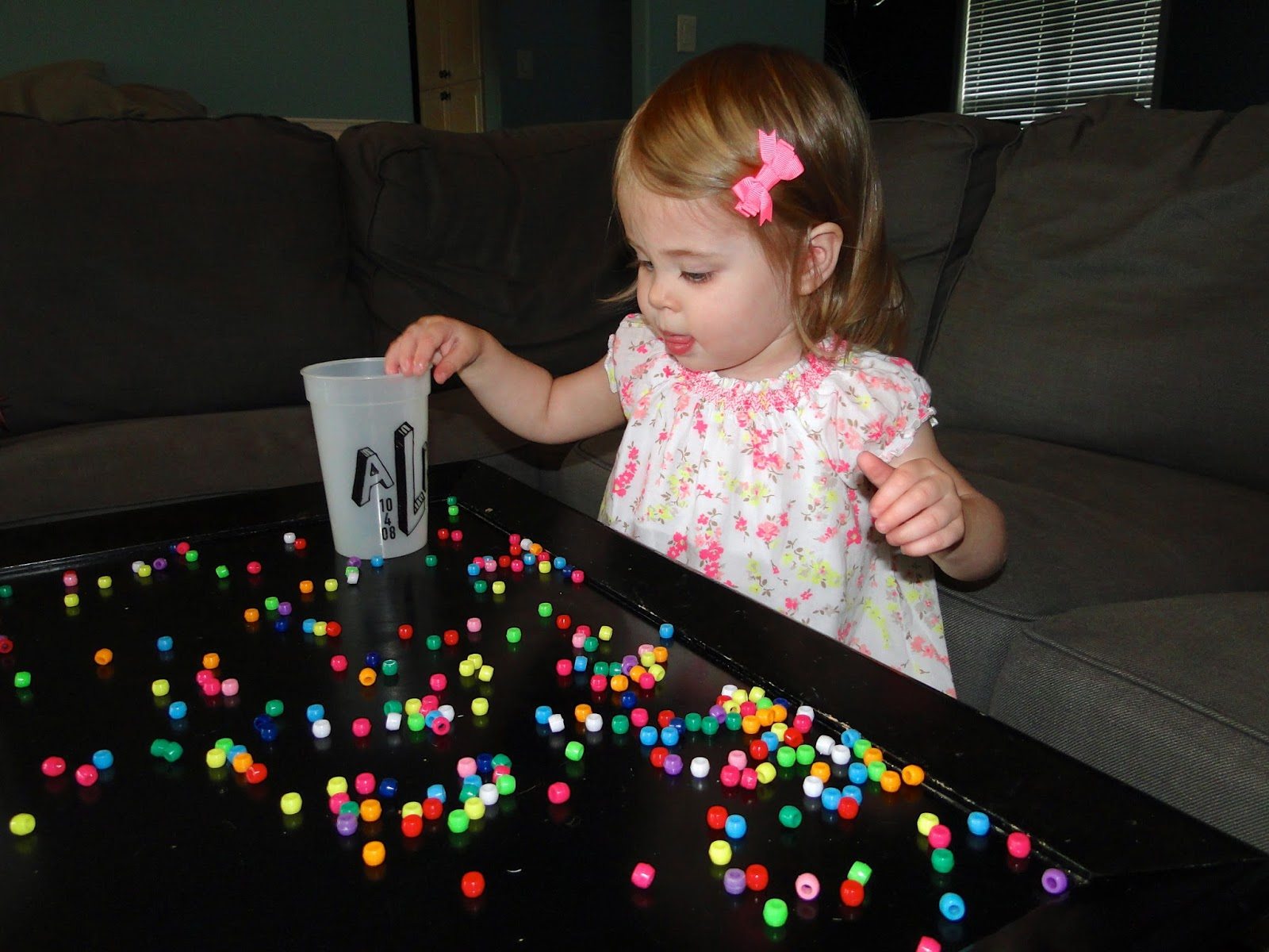 girl toddler playing with beads