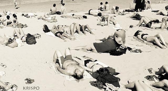gente tomando el sol en la playa pequeña de hondarribia