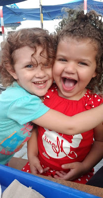 Two curly-haired blonde toddler girls hugging and smiling.
