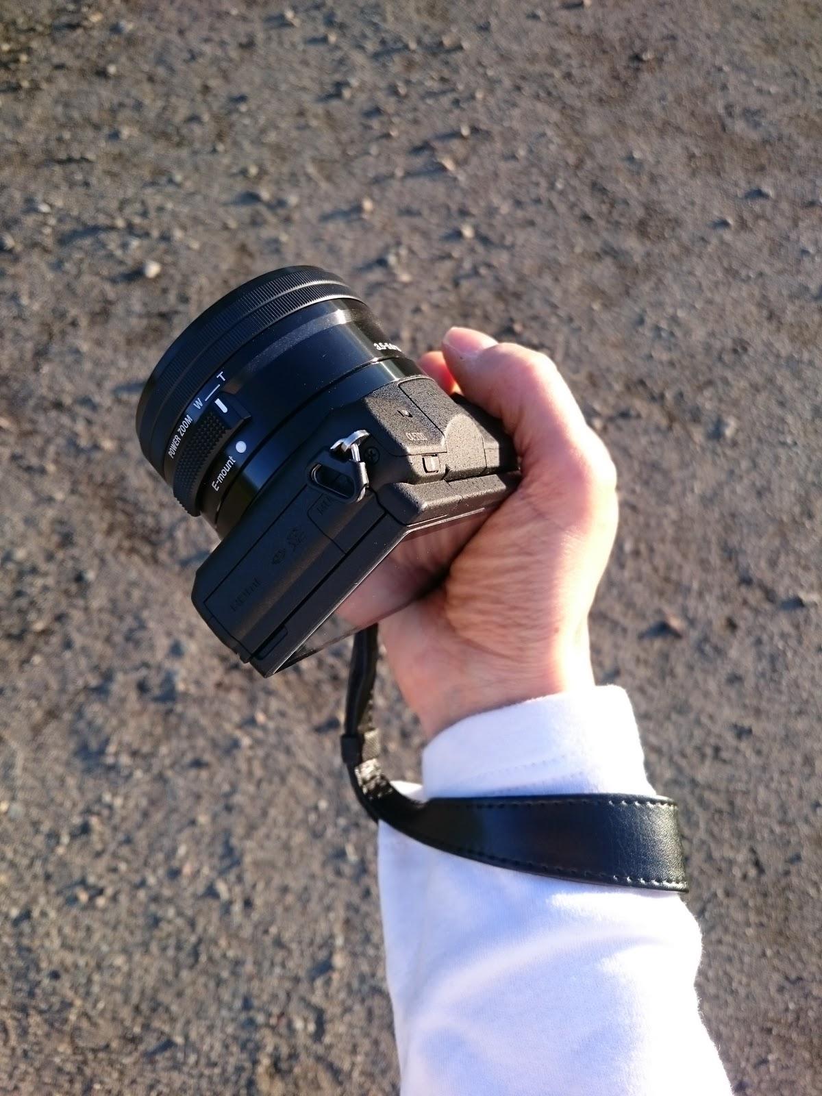 Sonyの一眼カメラのリストストラップのEマウント用のSTP-WS2の黒を付けてα5100を持っている右手