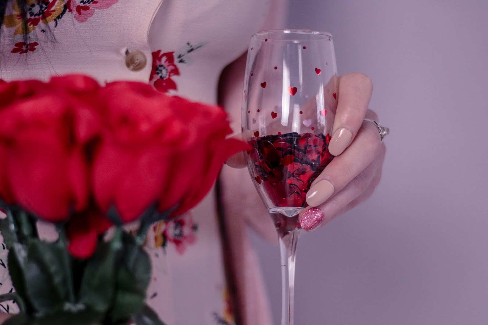 Close up photo of girl holding a champagne flute that had has red hearts on the glass with red faux Rose's in the other hand.