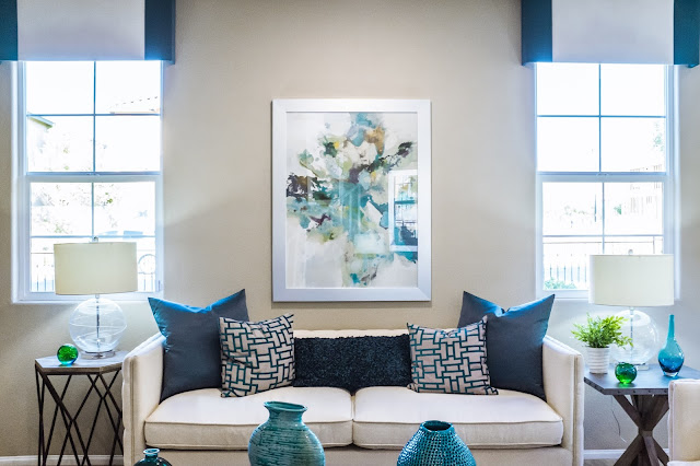 A cream sofa with teal cushions