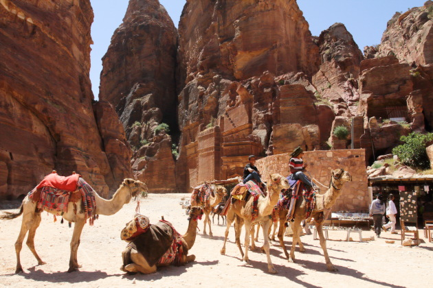 Camels and their riders at the entrance to the street of facades, Petra, Jordan