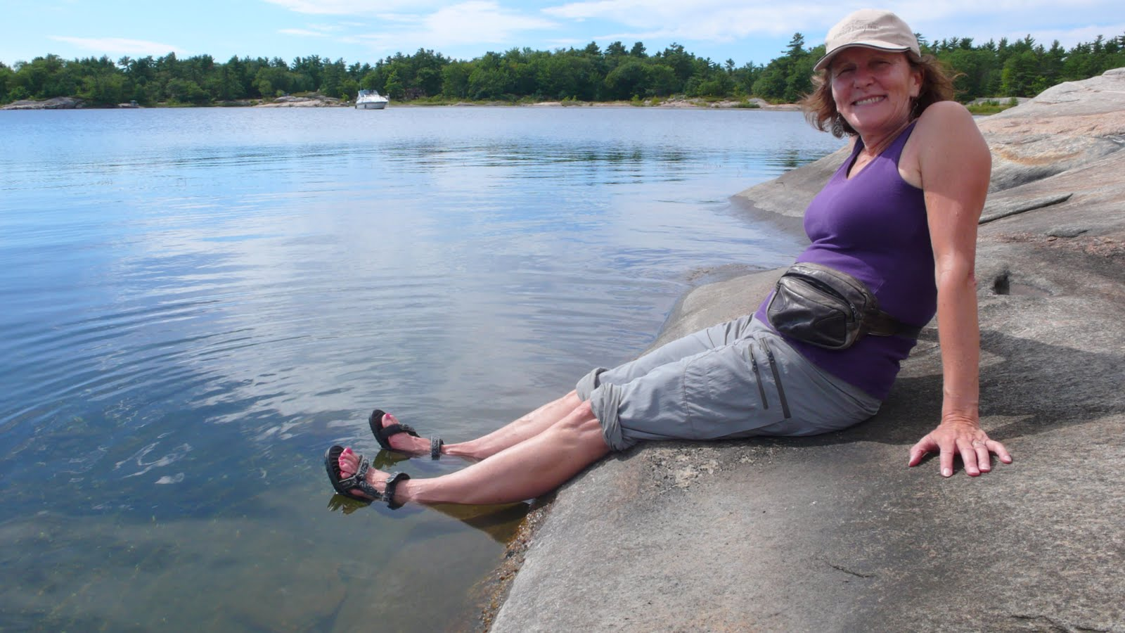 Liz sitting on rocks with feet in water