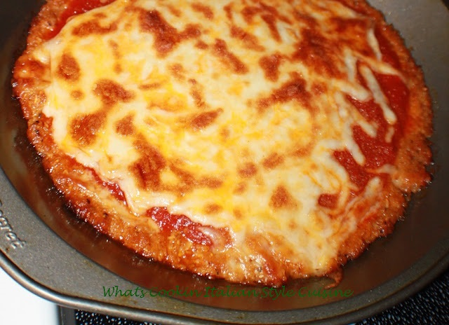 this is how to make a zucchini pizza crust into a real great tasting pizza. This is in a pie plate that is greased and sauce is on top with melted mozzarella cheese