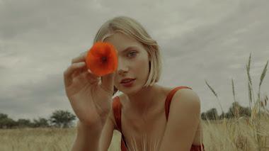 Chica rubia de ojos verdes y vestido rojo con flor roja en mano