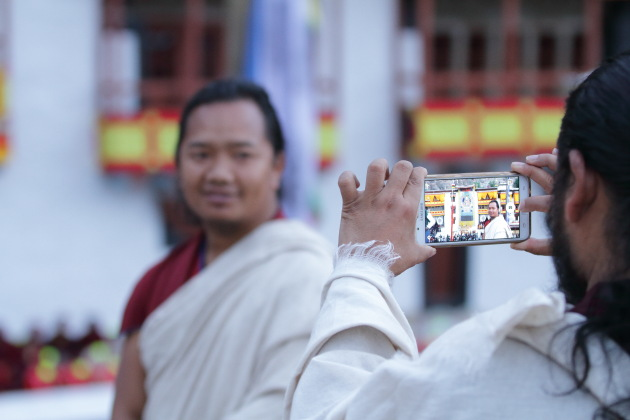 Hemis Monastery Monk getting his picture clicked in front of Guru Rinpoche Thangka
